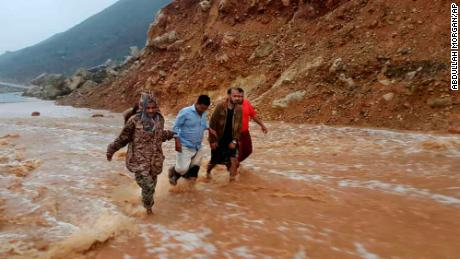Men walk on a flooded road Thursday as rain and winds from Cyclone Mekunu hit the island of Socotra