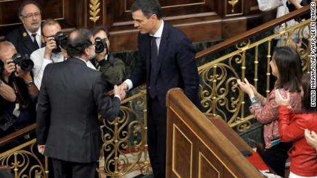 Outgoing Prime Minister Mariano Rajoy shakes hands with Spain's new Prime Minister Pedro Sanchez after Friday's vote.