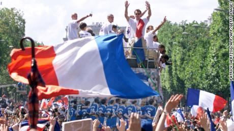 Players of the victorious French national team wave to supporters during a parade on Champs Elysees.