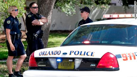 Orlando police block an intersection leading to an apartment complex where an officer was shot and seriously wounded before the suspected gunman barricaded himself in an apartment with young children.
