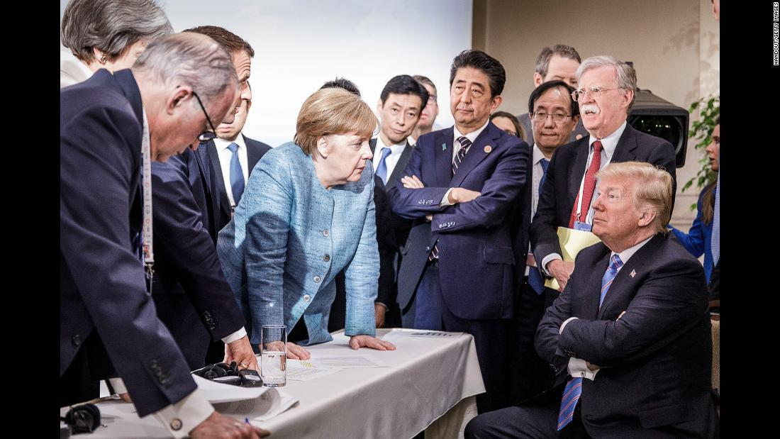 In this photo provided by the German Government Press Office, German Chancellor Angela Merkel talks with US President Donald Trump, seated, as they are surrounded by other leaders at the G7 summit in Charlevoix, Quebec, on Saturday, June 9. According to two senior diplomatic sources,  the photo was taken  when there was a difficult conversation taking place regarding the G7's communique and several issues the United States had leading up to it.
