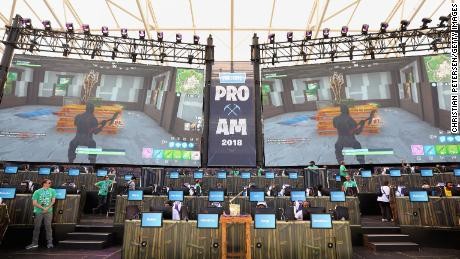The Fortnite trophy is displayed in the foreground as gamers compete in Epic Games' Fortnite E3 Tournament.