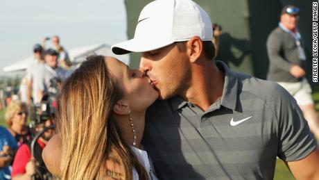 Brooks Koepka kisses girlfriend Jena Sims as he walks off the 18th at Shinneock Hills.