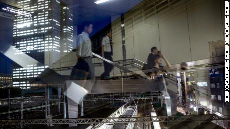 Japanese office workers are seen reflected in a window as they walk to a train station.