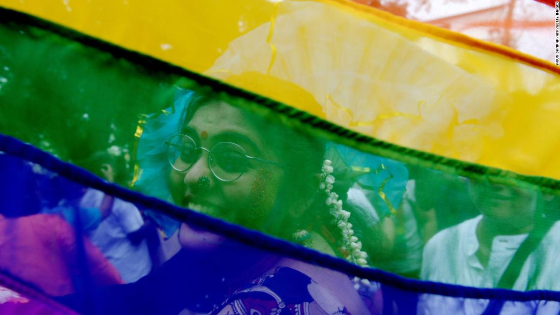 A supporter is seen through a rainbow flag at a Pride parade in Chennai, India, on Sunday.