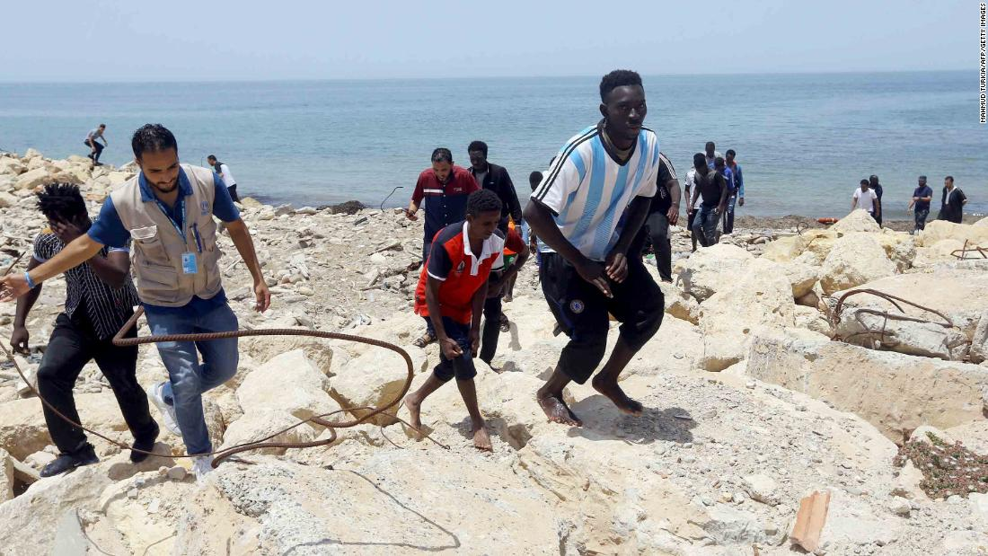 Migrants who survived the sinking climb the rocky shore of al-Hmidiya, east of the capital Tripoli.