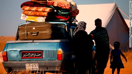 Displaced Syrians wait in a makeshift camp to cross the Jordanian border