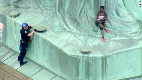 Climber, protesters at Statue of Liberty