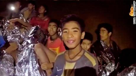 Some of the trapped children smile when a Thai Navy SEAL doctor offers assistance inside the cave on Tuesday.