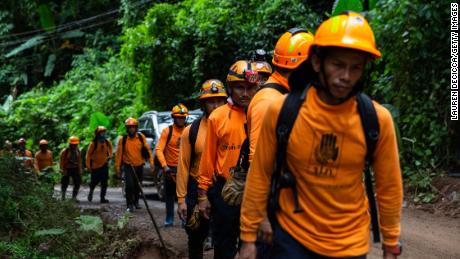 Men from the Department of Disaster Prevention and Mitigation arrive at the entrance to the cave on July 6, in Chiang Rai, Thailand.