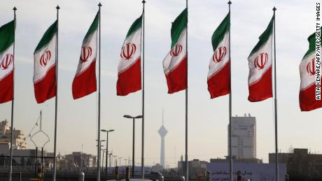 Tehran's landmark Milad Tower is seen through a row of national flags in the center of the Iranian capital