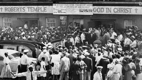 A crowd gathers outside the Roberts Temple Church of God In Christ in Chicago in 1955 as pallbearers carry the casket of Emmett Till.