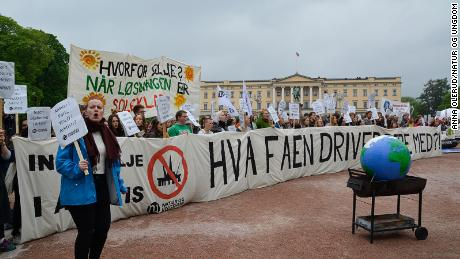 """Nature and Youth members demonstrate outside a Norwegian cabinet meeting with a sign that reads: """"What the hell are you doing?"""""""