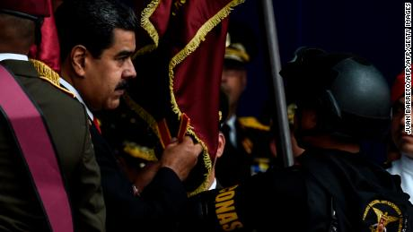 "Venezuelan President Nicolas Maduro (L) attends a ceremony to celebrate the 81st anniversary of the National Guard in Caracas on August 4, 2018. - Maduro was unharmed after an exploding drone ""attack"", the minister of communication Jorge Rodriguez said following the incident, which saw uniformed military members break ranks and scatter after a loud bang interrupted the leader's remarks and caused him to look to the sky, according to images broadcast on state television. (Photo by Juan BARRETO / AFP)        (Photo credit should read JUAN BARRETO/AFP/Getty Images)"