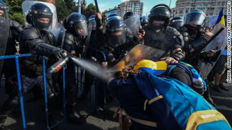 Romanian police scuffle with protesters during an anti-government protest in Bucharest on Friday
