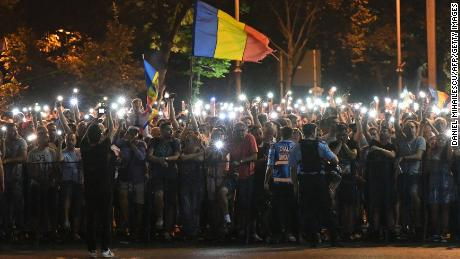 People wave Romanian national flags during Saturday's rally
