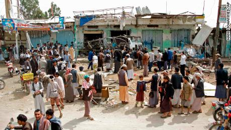 People gather on August 12 at the site of the deadly airstrike in Saada.