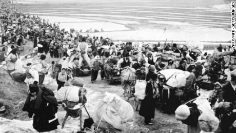 Picture taken on January, 18, 1951 shows Korean refugees fleeing to the south, as they pass by frozen rice fields.