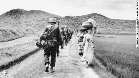 US soldiers pass fleeing refugees in the Nakdong River region, in what is now South Korea, during the Korean War.