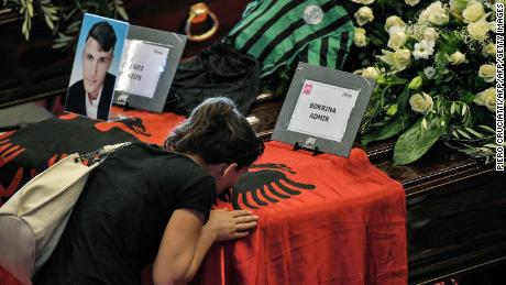 A relative of an Albanian victim of the bridge collapse kisses the flag covering the coffin ahead of the funeral service Saturday in Genoa