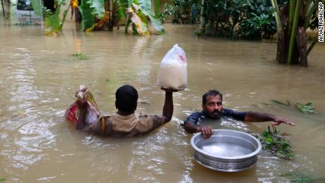 An Indian policeman, left, and a volunteer carry essential supplies for stranded people in a flooded area in Chengannur in the southern state of Kerala, India, Sunday, August 19.