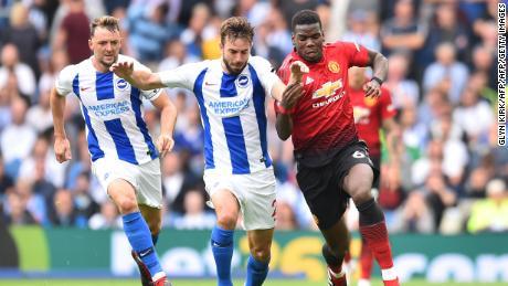 Pogba (R) challenges Brighton's Dutch midfielder Davy Propper (C).