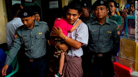 Detained Myanmar journalist Kyaw Soe Oo hugs his daughter as he is escorted by police to a courtroom for his on going trial in Yangon on July 17, 2018.