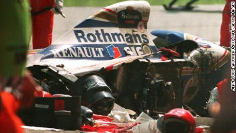 Security personnel surround the crashed car of Brazilian Formula One driver Ayrton Senna.