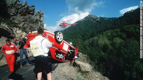 Mäkinen (left) inspects his car after a crash during Rally Corsica in 2001.
