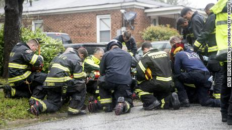 Firefighters and rescue crew pray in front of a home after removing a resident trapped inside due to a fallen tree during Hurricane Florence in Wilmington North Carolina U.S. on Friday Sept. 14 2018. Hurricane Florence is delivering driving wind