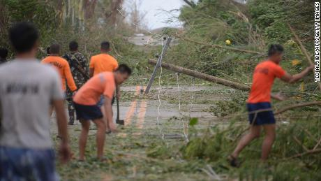 Rescue workers clear a road of debris and toppled electric posts in Cagayan province, north of Manila on Saturday.