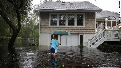 Kim Adams wades through floodwaters surrounding her home Saturday in Southport, North Carolina.