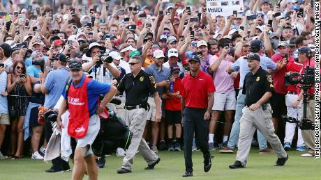 Tiger Woods is swarmed by fans as he walks to the 18th green during the final round of the TOUR Championship.