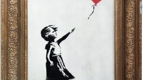 Banksy painting 'self-destructs' moments after being sold for $1.4 million at auction