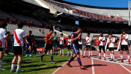 "The ""Wild Boars"" team enter the field for the friendly match against River Plate's youth team."