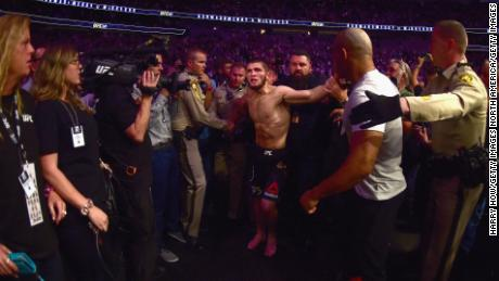 Khabib Nurmagomedov is escorted out of the arena after defeating Conor McGregor in their UFC lightweight championship bout.
