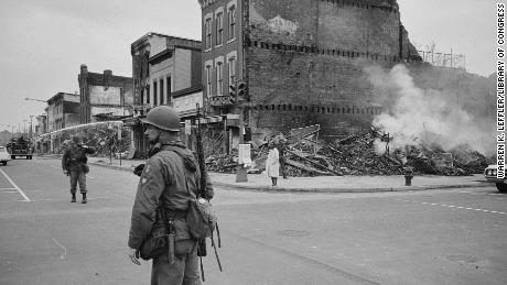 A soldier stands guard in Washington near buildings that were destroyed in the riots that followed the assassination of Martin Luther King, Jr. in April 1968.