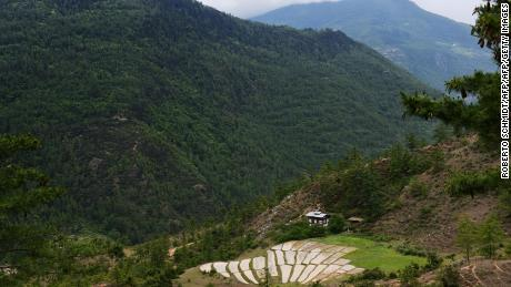 The house of a working farm sits in a valley nestled in the mountains near the eastern Bhutanese town of Paro.