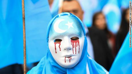 A person wearing a white mask with tears of blood takes part in a protest march of ethnic Uyghurs asking for the European Union to call upon China to respect human rights in the Chinese Xinjiang region in April.