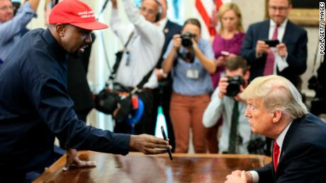 Rapper Kanye West, on the left, shows a picture of an airplane on a telephone to the President of the United States, Donald Trump, during a meeting at the White House Oval Office on October 11, 2018 in Washington, DC.