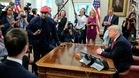 Rapper Kanye West, second from left, stands up while speaking during a meeting with US President Donald Trump at the White House Oval Office on October 11, 2018 in Washington, DC.