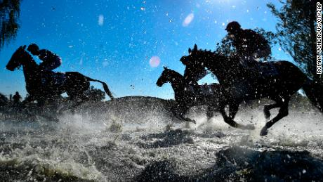 Horses and jockeys compete during the Steeplechase cross country in Pardubice, Czech Republic.