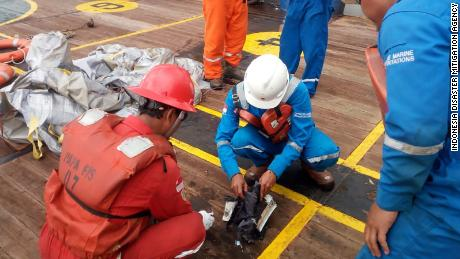 Officials examine debris suspected to be from a crashed Lion Air flight.