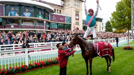 Frankie Dettori performs his trademark flying dismount after Enable won her first Arc in 2017.