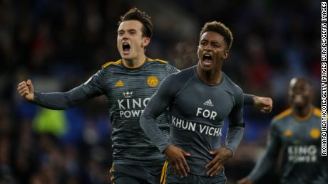 Demarai Gray celebrates with teammate Ben Chilwell, revealing a commemorative message for Vichai Srivaddhanaprabha during the Premier League match between Cardiff City and Leicester City.