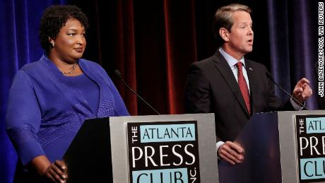 Republican gubernatorial candidate Brian Kemp speaks as Democratic rival Stacey Abrams looks on during a debate in Atlanta on October 23, 2018.
