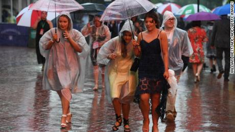 Race-goers take shelter from the rain ahead of the Melbourne Cup.