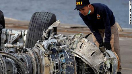 The Indonesian National Transportation Safety Commission (KNKT) official examines a turbine engine from the Lion Air crash.
