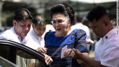 Imelda Marcos is assisted to her car after visiting her husband's tomb