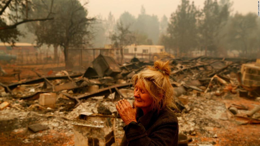 Cathy Fallon reacts as she stands near the charred remains of her home November 9 in Paradise.